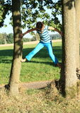 Little kid - girl climbing on trunks Royalty Free Stock Photography