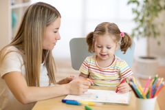 Little kid girl coloring with felt pen next to her mother in nursery room. Little child girl coloring with felt pen next to her mother in nursery room Stock Image