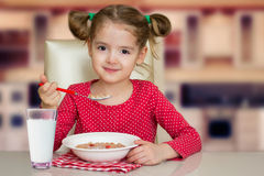 Little kid girl eating milk snack at the kitchen table. Stock Photos
