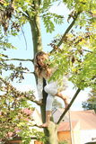 Little kid - girl hanging on branch Stock Photography