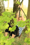 Little kid - girl hanging on branch Stock Image