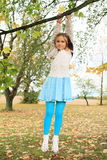 Little kid - girl hanging on branch Stock Photo
