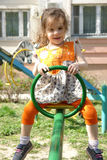 Little kid girl having fun on playground on sunny spring day Stock Images