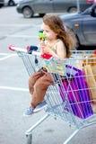 Little kid girl having fun sitting in a shopping trolley near the mall. Little kid girl having fun sitting in a shopping trolley near the mall Royalty Free Stock Photos