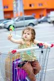 Little kid girl having fun sitting in a shopping trolley near the mall. Little kid girl having fun sitting in a shopping trolley near the mall Stock Photos