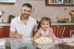 Little kid girl help man to cook lazy dumplings in light kitchen at table. Happy family dad, child daughter cooking food. Little kid girl help men to cook lazy royalty free stock photography