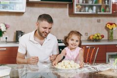 Little kid girl help man to cook lazy dumplings in light kitchen at table. Happy family dad, child daughter cooking food. Little kid girl help men to cook lazy royalty free stock photo