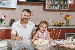 Little kid girl help man to cook lazy dumplings in light kitchen at table. Happy family dad, child daughter cooking food. Little kid girl help men to cook lazy royalty free stock images