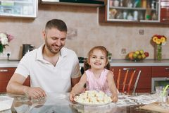 Little kid girl help man to cook lazy dumplings in light kitchen at table. Happy family dad, child daughter cooking food. Little kid girl help men to cook lazy royalty free stock photos