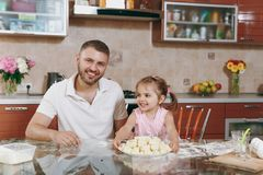 Little kid girl help man to cook lazy dumplings in light kitchen at table. Happy family dad, child daughter cooking food. Little kid girl help men to cook lazy stock photos