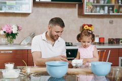 Little kid girl help man to cook Christmas ginger cookies, gives eggs in kitchen at table. Happy family dad, child stock photography