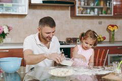 Little kid girl help man to cook lazy dumplings sprinkling flour at table. Happy family dad, child daughter cooking food. Little kid girl help men to cook lazy royalty free stock image