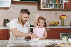 Little kid girl helps man to cook Christmas ginger cookies in kitchen at table. Happy family dad, child daughter cooking. Little kid girl helps men to cook stock photo