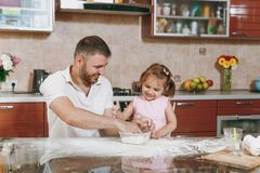 Little kid girl helps man to cook Christmas ginger cookies in kitchen at table. Happy family dad, child daughter cooking. Little kid girl helps men to cook royalty free stock photo