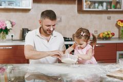 Little kid girl helps man to cook Christmas ginger cookies in kitchen at table. Happy family dad, child daughter cooking stock photography