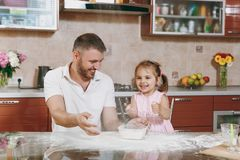 Little kid girl helps man to cook Christmas ginger cookies, playing with flour at table. Happy family dad, child stock images