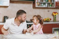 Little kid girl helps man to cook Christmas ginger cookies, playing with flour at table. Happy family dad, child stock photography