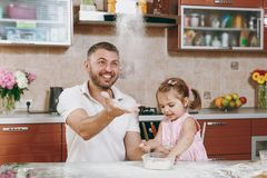 Little kid girl helps man to cook Christmas ginger cookies, playing, sprinkling flour at table. Happy family dad, child stock photography