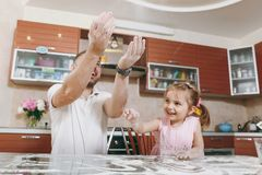 Little kid girl helps man to cook Christmas ginger cookies, sprinkling flour in kitchen at table. Happy family dad stock image