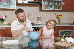 Little kid girl helps man to cook Christmas ginger cookies, stirs dough in bowl at table. Happy family dad, child royalty free stock photos