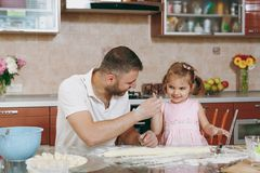 Little kid girl helps man to cook lazy dumplings, play in light kitchen at table. Happy family dad, child daughter stock photos
