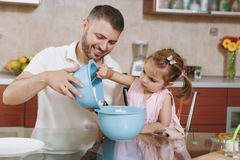 Little kid girl helps man to cook and pours cottage cheese into bowl in kitchen at table. Happy family dad, child royalty free stock photos