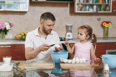 Little kid girl helps man to cook Christmas ginger cookies, breaks egg into bowl at table. Happy family dad, child. Little kid girl helps men to cook Christmas stock photos