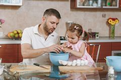 Little kid girl helps man to cook Christmas ginger cookies, breaks egg into bowl at table. Happy family dad, child. Little kid girl helps men to cook Christmas royalty free stock images