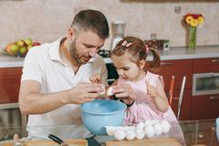Little kid girl helps man to cook Christmas ginger cookies, breaks egg into bowl at table. Happy family dad, child. Little kid girl helps men to cook Christmas stock photography