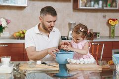 Little kid girl helps man to cook Christmas ginger cookies, breaks egg into bowl at table. Happy family dad, child. Little kid girl helps men to cook Christmas stock image