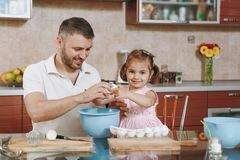 Little kid girl helps man to cook Christmas ginger cookies, breaks egg into bowl at table. Happy family dad, child. Little kid girl helps men to cook Christmas stock images