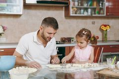 Little kid girl helps man to cook lazy dumplings, cutting dough at table. Happy family dad, child daughter cooking food. Little kid girl helps men to cook lazy stock photography