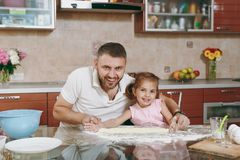 Little kid girl helps man to cook lazy dumplings, forming dough at table. Happy family dad, child daughter cooking food. Little kid girl helps men to cook lazy royalty free stock photos