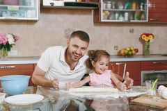 Little kid girl helps man to cook lazy dumplings, forming dough at table. Happy family dad, child daughter cooking food. Little kid girl helps men to cook lazy royalty free stock images