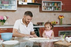 Little kid girl helps man to cook lazy dumplings, forming dough at table. Happy family dad, child daughter cooking food. Little kid girl helps men to cook lazy royalty free stock image