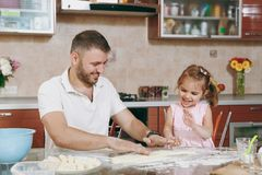 Little kid girl helps man to cook lazy dumplings, forming dough at table. Happy family dad, child daughter cooking food. Little kid girl helps men to cook lazy royalty free stock photo