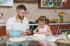 Little kid girl helps man to cook lazy dumplings, forming dough at table. Happy family dad, child daughter cooking food stock photos