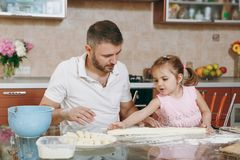 Little kid girl helps man to cook lazy dumplings, forming dough at table. Happy family dad, child daughter cooking food. Little kid girl helps men to cook lazy royalty free stock photography