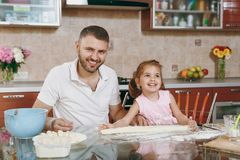 Little kid girl helps man to cook lazy dumplings, forming dough at table. Happy family dad, child daughter cooking food. Little kid girl helps men to cook lazy stock photos