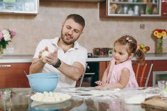Little kid girl helps man to cook lazy dumplings preparing dough at table. Happy family dad, child daughter cooking food. Little kid girl helps men to cook lazy stock photo