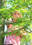Little kid - girl hiding behind leaves Stock Photos