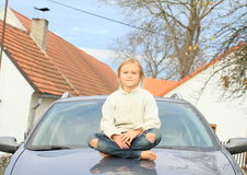 Little kid - girl on hood of car Stock Image