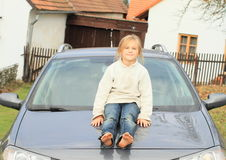 Little kid - girl on hood of car Stock Photography