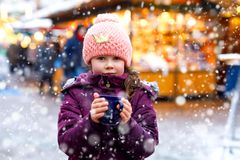 Little kid girl with hot chocolate on Christmas market. Little cute kid girl with cup of steaming hot chocolate or children punch. Happy child on Christmas stock photos