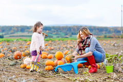 Little kid girl and mother having fun on pumkin Stock Photo