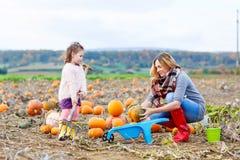 Little kid girl and mother having fun on pumkin Stock Photo
