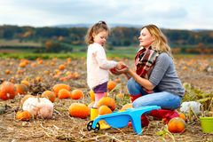 Little kid girl and mother having fun on pumkin field. Little kid girl and beautiful mother having fun with farming on a pumpkin patch. Traditional family royalty free stock photography