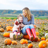 Little kid girl and mother having fun on pumkin field Royalty Free Stock Photography