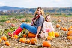 Little kid girl and mother having fun on pumkin Stock Photos