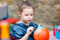 Little kid girl painting with colors on pumpkin Stock Photo